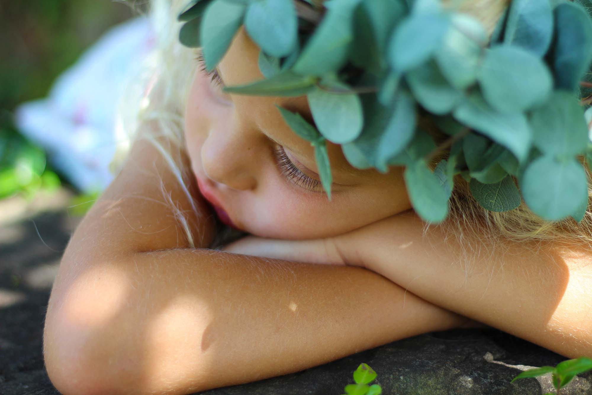 beautiful girl portrait lying on stone with plant crown