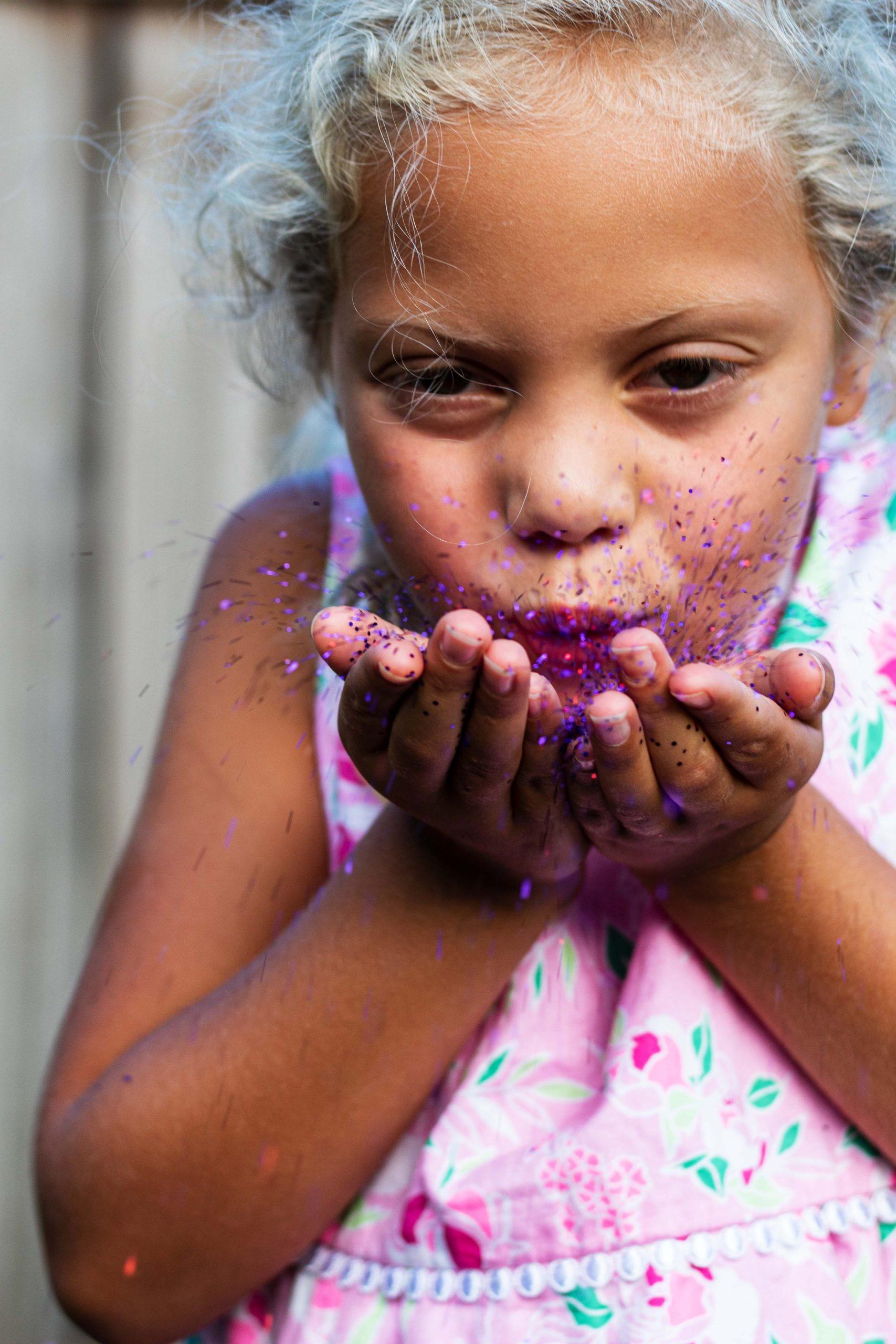 beautiful girl blowing pink glitter