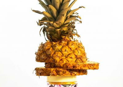 pineapple body scrub between a pineapple in front of glowing yellow background