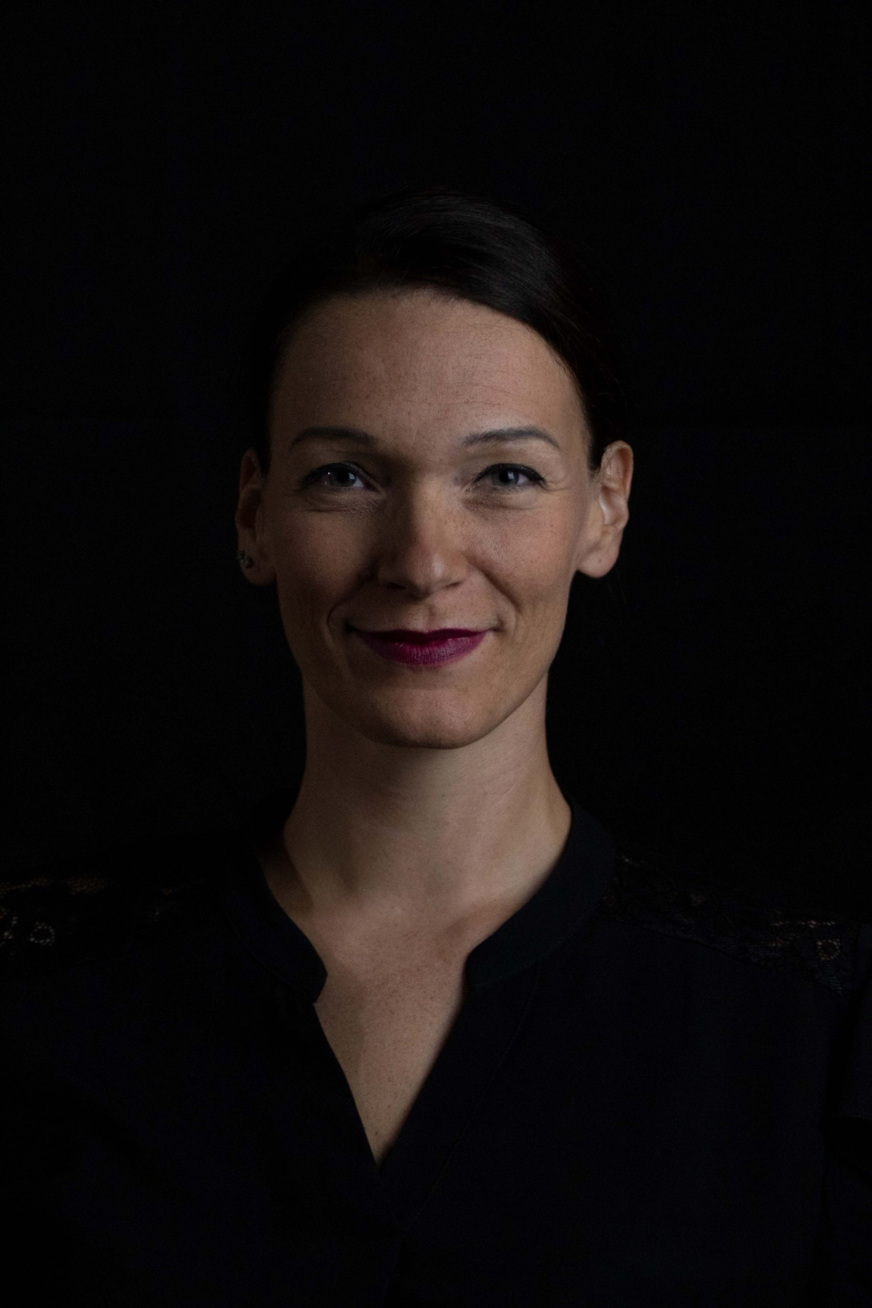 business woman in front of black background head shot