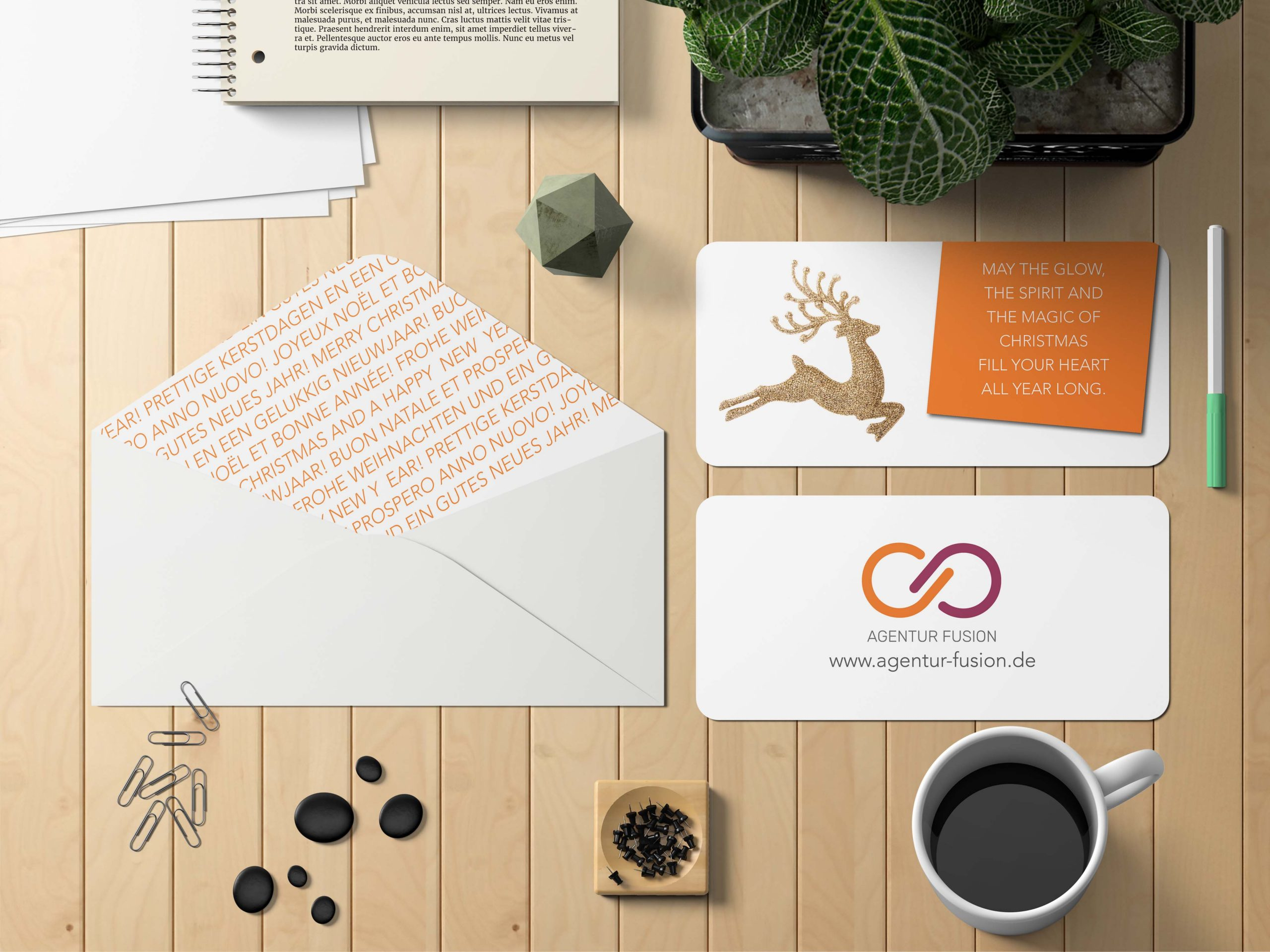 stationery with christmas card and envelope on desk with office stuff around