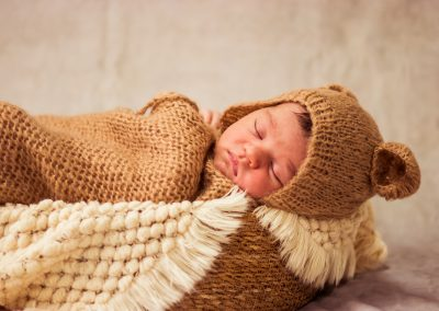 baby sleeping with bear heat in natural basket and blanket